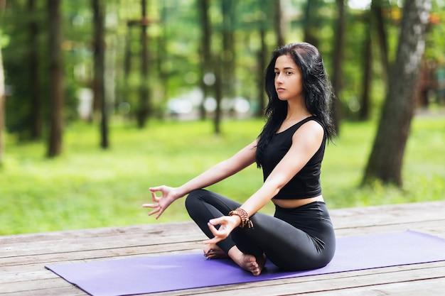 Junge frau in der schwarzen sportbekleidung meditiert im park auf einem hölzernen spielplatz