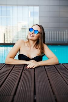 Junge frau in der sonnenbrille mit einem perfekten weißen lächeln, das in den ferien in einem pool badet