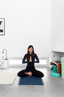 Junge frau in der sportbekleidung, die im lotussitz mit namaste händen sitzt und während der yogapraxis zu hause meditiert