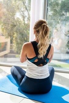 Junge frau in der sportbekleidung, die yoga auf matte drinnen in der klasse praktiziert. konzept des gesundheitslebensstils
