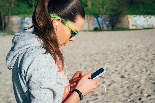 Junge frau in der sportkleidung mit einer haube gehend auf den strand und musik mit kopfhörern an einem intelligenten telefon hörend