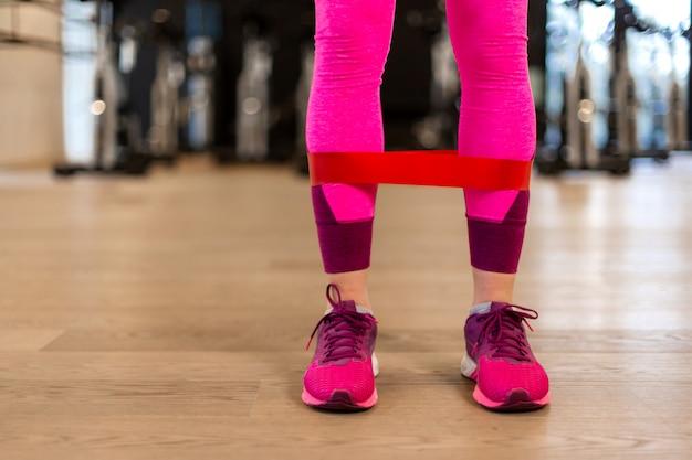 Junge frau in der sportwear sportübung mit sitzgummiband auf beinen in der turnhalle.
