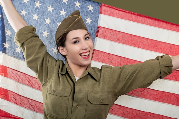 Junge frau in der us-militäruniform, die eine amerikanische flagge hält.