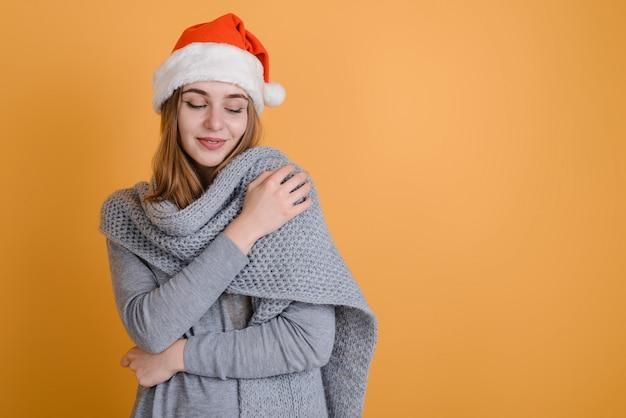 Junge frau in der warmen strickjacke und im sankt-hut auf orange hintergrund