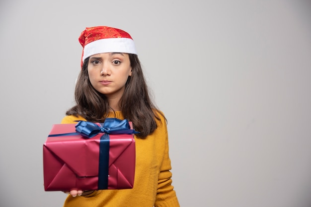 Junge frau in der weihnachtsmannmütze, die eine geschenkbox zeigt.
