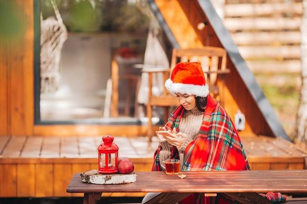 Junge frau in der weihnachtsmütze, die auf dem hölzernen alten tischhintergrund ihres hauses sitzt