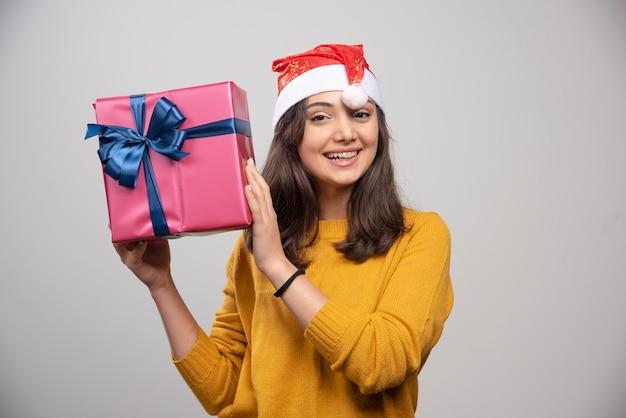 Junge frau in der weihnachtsmütze, die eine geschenkbox hält.