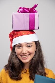 Junge frau in der weihnachtsmütze, die geschenkboxen über kopf hält.