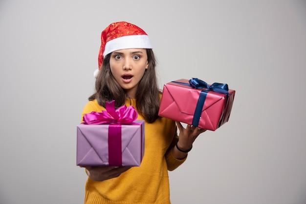 Junge frau in der weihnachtsmütze, die in den weihnachtsgeschenken der hände hält.