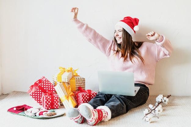 Junge frau in der weihnachtsmütze, die online einkauft, umgeben von geschenken