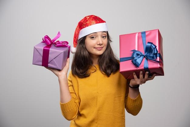 Junge frau in der weihnachtsmütze, die weihnachtsgeschenke trägt.