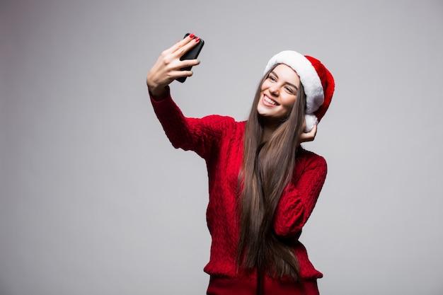Junge frau in der weihnachtsmütze nehmen selfie am telefon lokalisiert auf grauer wand