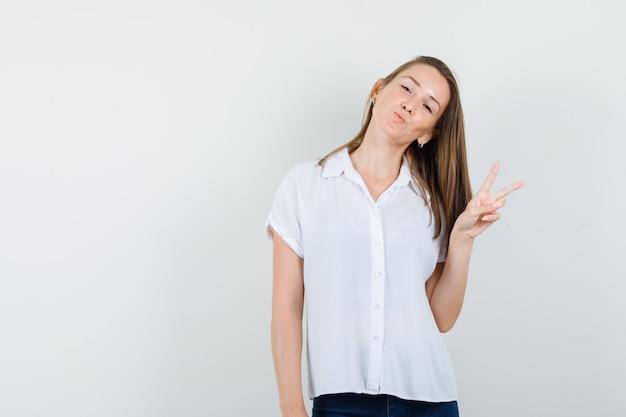 Junge frau in der weißen bluse, die friedensgeste zeigt, während sie ihren hals zur seite beugt und entspannt aussieht