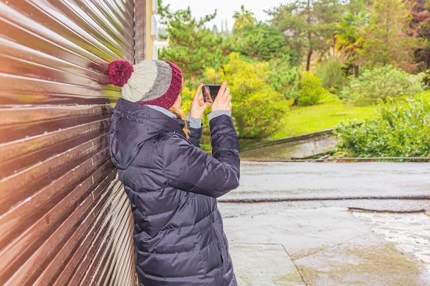 Junge frau in der winterkleidung macht ein foto auf einem telefon der natürlichen landschaft, seitenansicht. touristinnen gehen im park spazieren.