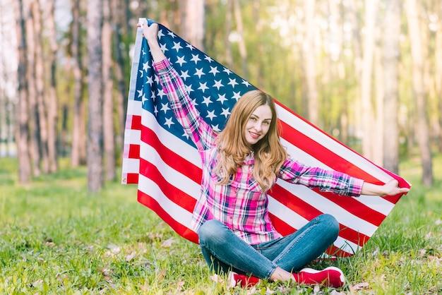 Junge frau in der zufälligen kleidung, die auf dem boden sitzt und amerikanische flagge hält