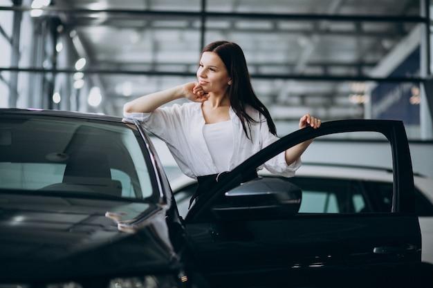 Junge frau in einem autosalon, der ein auto wählt