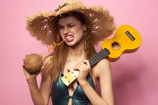 Junge frau in einem badeanzug und einem hut mit ananas in der hand, spaßparty, strand zu hause, der ukulele gitarre spielt
