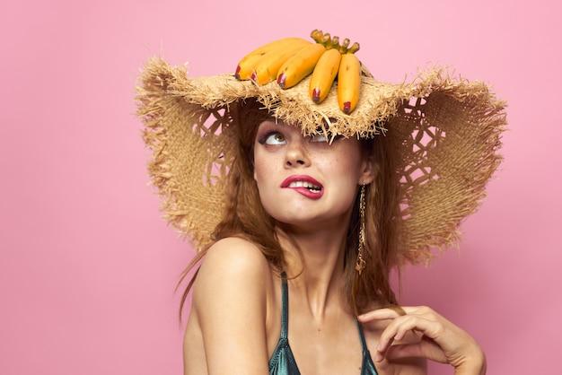 Junge frau in einem badeanzug und einem hut mit ananas in der hand, spaßparty, strand zu hause
