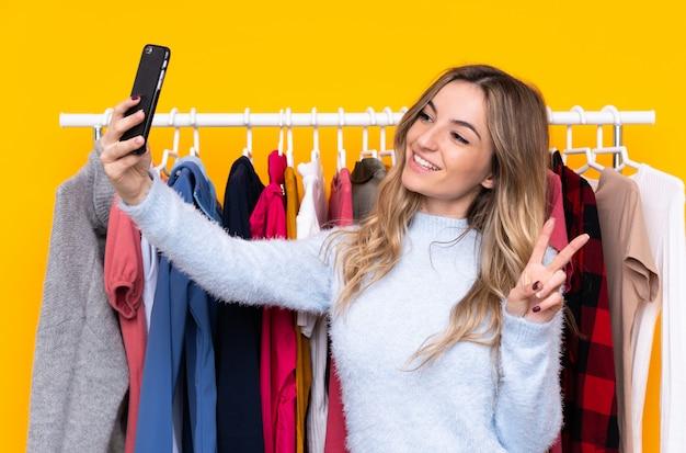 Junge frau in einem bekleidungsgeschäft mit einem mobile über lokalisierter gelber wand