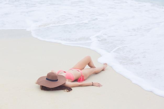 Junge frau in einem bikini, der auf dem sandstrand und -wellen liegt