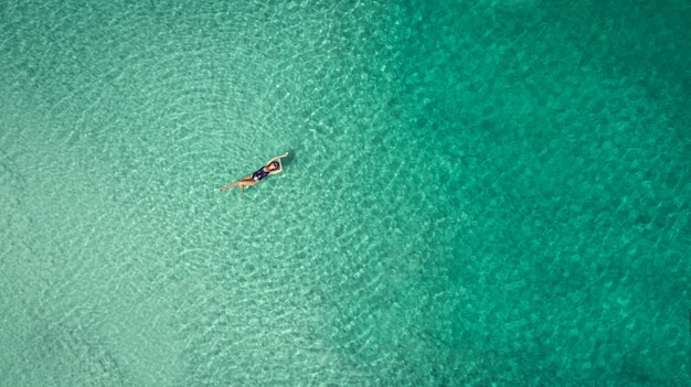 Junge frau in einem bikini, der auf der rückseite auf dem weißen sand nahe den wellen von blauem meer liegt