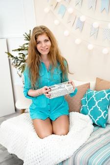 Junge frau in einem blauen hemd mit geschenk vor weihnachten zu hause, gemütliches helles interieur