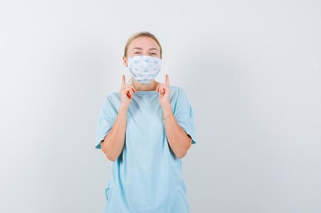 Junge frau in einem blauen t-shirt mit einer medizinischen maske