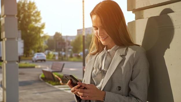 Junge frau in einem business-anzug mit einem telefon steht auf der straße, sonnenlicht