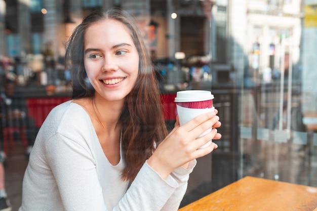 Junge frau in einem café, das einen kaffee genießt - schöne brünette, die hinter einem fenster in einer café-bar in london sitzt und von der kamera wegschaut, roter bus im spiegelbild - lifestyle- und essensgetränkekonzepte