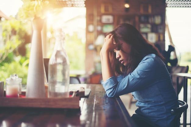 Junge frau in einem café mit ihrem laptop sitzen, belastend für wor