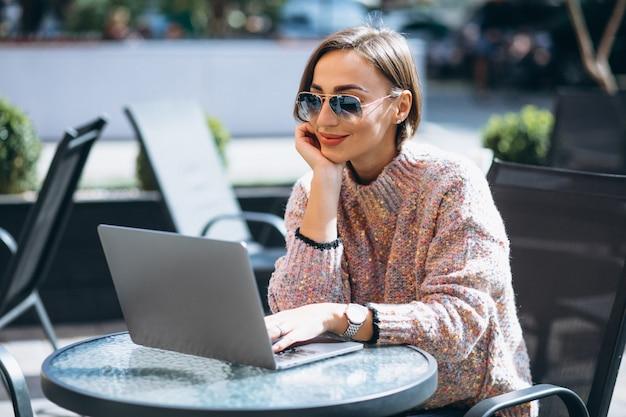 Junge frau in einem café unter verwendung des laptops