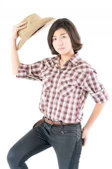 Junge frau in einem cowboyhut und in einem karierten hemd mit der hand auf ihrem hut