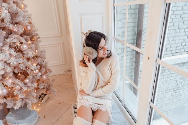 Junge frau in einem eleganten kleid nahe dem weihnachtsbaum