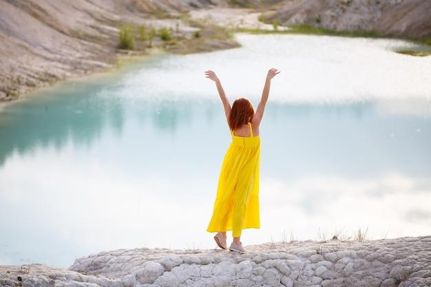 Junge frau in einem gelben kleid nahe dem see mit azurblauem wasser und grünen bäumen.