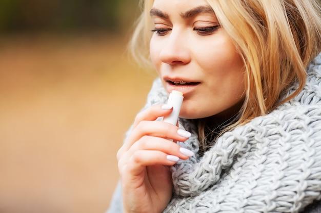 Junge frau in einem grauen mantel benutzen hygienischen lippenstift im herbstpark