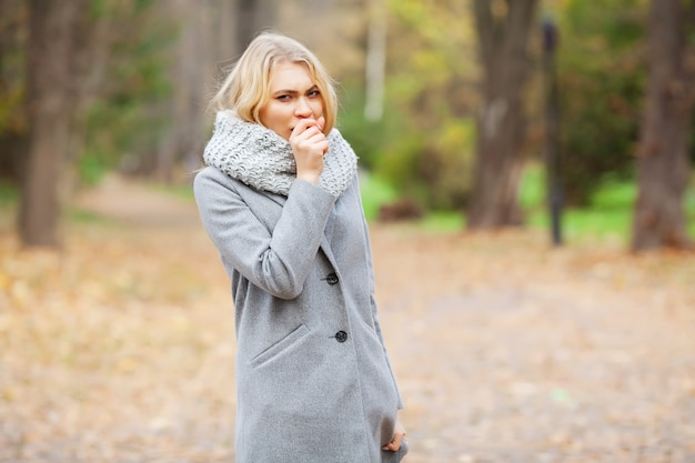 Junge frau in einem grauen mantel gehend in den herbstpark