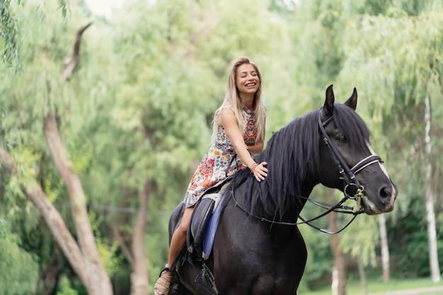 Junge frau in einem hellen bunten kleid, das ein schwarzes pferd reitet