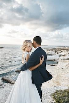 Junge frau in einem hochzeitskleid und bräutigam in einem anzug, der auf der klippe nahe dem ozean aufwirft. glückliches paar, das zusammen auf der schönen landschaft der seeküste von zypern umarmt.
