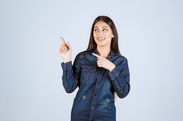 Junge frau in einem jeanshemd, das linke seite mit gesichtsgefühlen zeigt