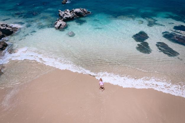 Junge frau in einem kleid, das auf dem rücken auf dem weißen sand nahe den wellen des blauen meeres liegt. draufsicht, andamanensee, phuket, thailand. antenne
