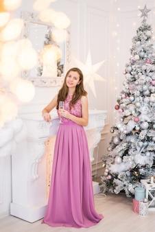 Junge frau in einem langen kleid, das neben weihnachtsbaum mit einem glas champagner in ihren händen aufwirft.