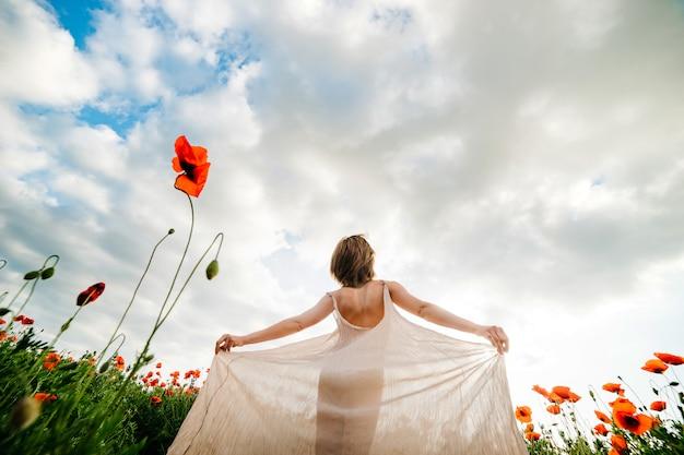 Junge frau in einem langen weißen kleid auf einem mohnblumengebiet gegen einen blauen himmel in den wolken