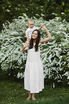 Junge frau in einem langen weißen kleid mit einem niedlichen kleinen jungen im hemd und in den kurzen hosen, die am grünen blühenden garten im sommertag gehen