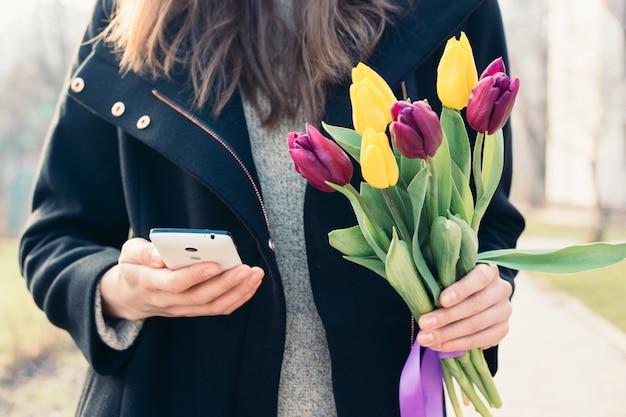 Junge frau in einem mantel, der einen blumenstrauß von tulpen in der einen hand und in der anderen hand handy hält