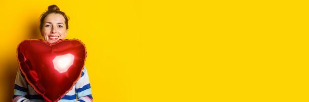 Junge frau in einem pullover hält ein luftballonherz auf gelbem hintergrund. valentinstag komposition.