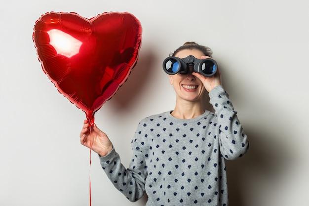 Junge frau in einem pullover schaut durch fernglas und hält ein luftballonherz auf einem hellen hintergrund. valentinstag konzept. suche nach einem geliebten menschen.