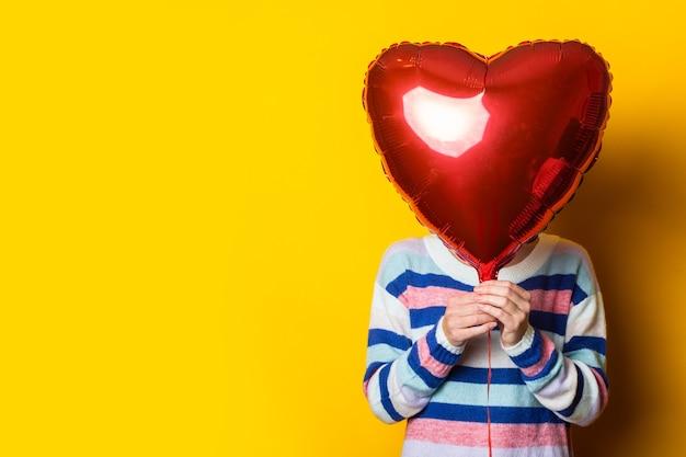 Junge frau in einem pullover versteckt sich hinter einem luftballonherz auf einem gelben hintergrund. valentinstag komposition.
