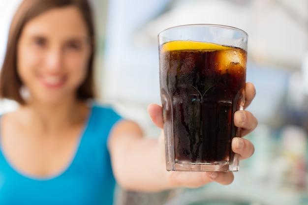 Junge frau in einem restaurant mit einer cola