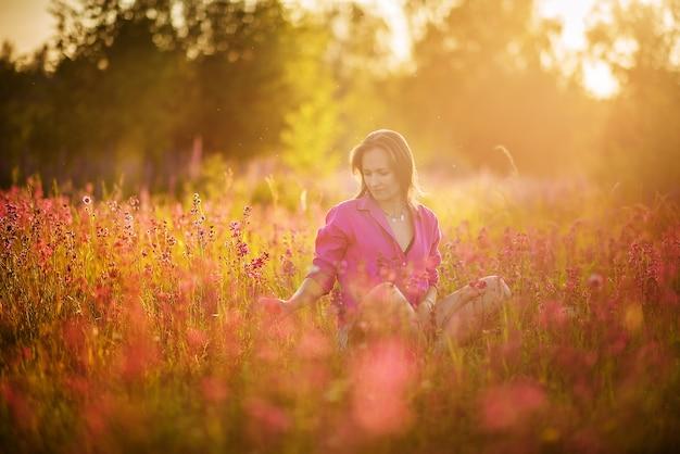 Junge frau in einem rosa hemd, das in einem blühenden feld sitzt.