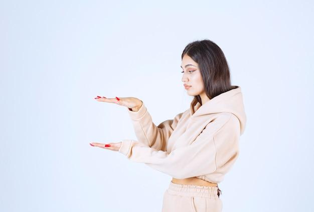 Junge frau in einem rosa kapuzenpulli, der die geschätzten maße eines objekts demonstriert